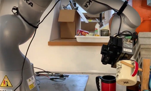 A robot holding a cup up